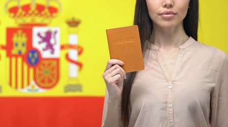 гражданство : Serious lady showing passport, isolated on Spanish flag background, election