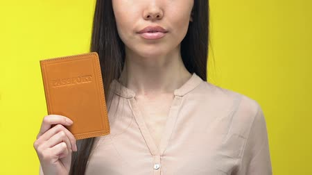 embassy : Businesswoman showing passport, migration service, isolated on yellow background Stock Footage
