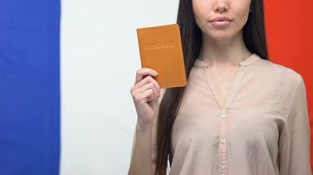 citizenship : Serious lady showing passport, French flag background international organization Stock Footage