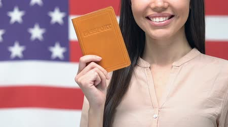 pasaport : Smiling woman showing passport against American flag, getting USA citizenship Stok Video