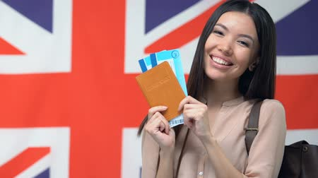 pasaport : Happy woman showing tickets and passport, English flag, travelling to Britain