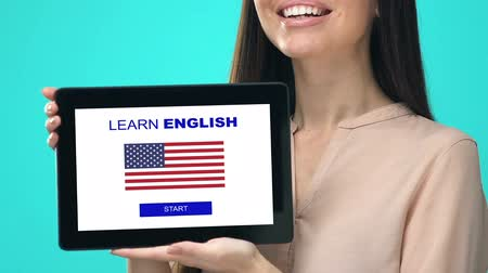 nativo americano : Glad female holding tablet with learn English app, USA flag on screen, education