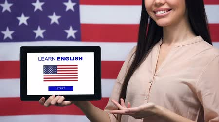 nativo americano : Smiling lady holding tablet with learn English language app, USA flag background