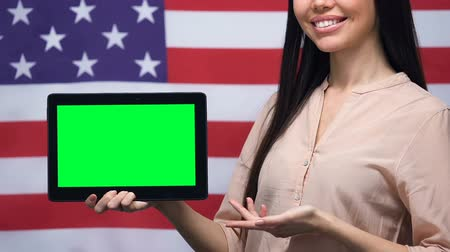 nativo americano : Woman showing green screen tablet, USA flag background, educational application
