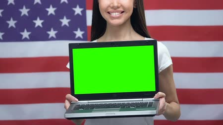 nativo americano : Laptop with green screen in female hands, USA flag background, education, travel