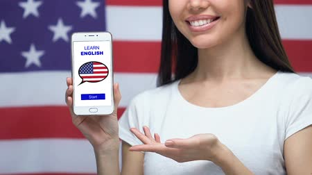 nativo americano : Learn English language app on cellphone in female hand, USA flag on background Stock Footage