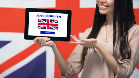 derece : Learn English app on tablet screen in female hand, Great Britain flag background Stok Video