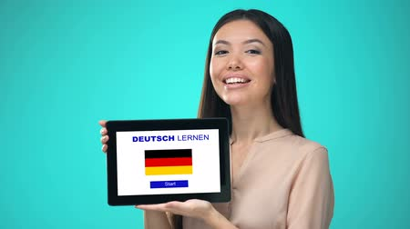 gramatika : Female holding tablet with learn german application, ready to start course