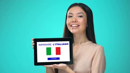 nyelv : Female holding tablet with learn italian application, ready to start course