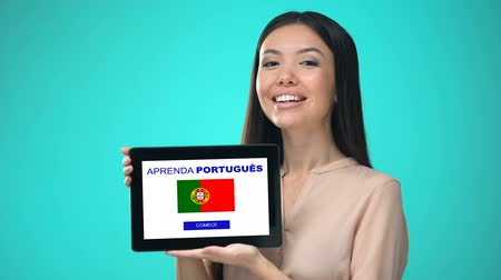 regulamin : Female holding tablet with learn portuguese application, ready to start course