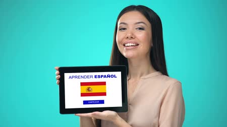 regulamin : Female holding tablet with learn spanish application, ready to start course