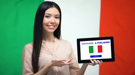 スペル : Lady holding tablet with learn Italian app, Italy flag on background, education