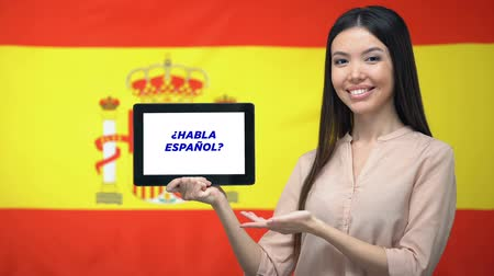 gramatika : Woman holding tablet with do you speak spanish phrase, app for learning language