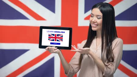 gramatika : Lady holding tablet with learn English app, Great Britain flag on background Dostupné videozáznamy
