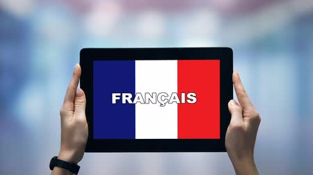 гимназия : Female hands holding tablet with French word against national flag, online app