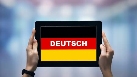 gramatika : Female hands holding tablet with German word against national flag, online app