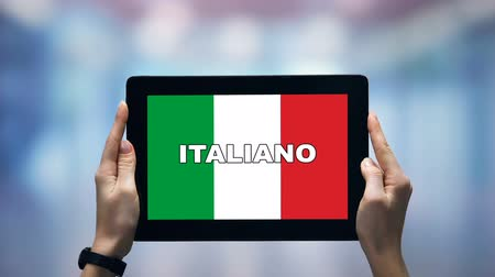 gramatika : Female hands holding tablet with Italian word against national flag, online app