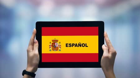 гимназия : Female hands holding tablet with Spanish word against national flag, online app Стоковые видеозаписи