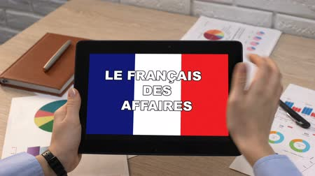 zahraniční : Business French application against flag on tablet in female hands, tutorial
