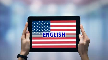 bandeira americana : Female hands holding tablet with English word against USA flag, online app