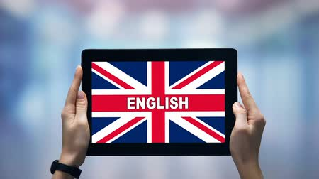 zahraniční : Female hands holding tablet with English word against Britain flag, online app