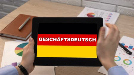 грамматика : Business German application against flag on tablet in female hands, tutorial