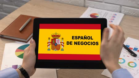 gramatika : Business Spanish application against flag on tablet in female hands, tutorial