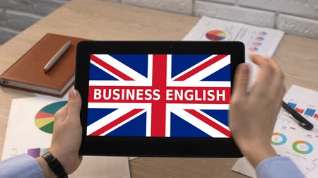 гимназия : Business English app against Britain flag on tablet in female hands, tutorial