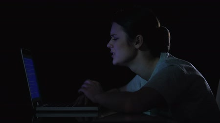 download : Teenager girl crying because of problems with laptop, sitting in dark room