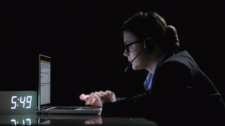 yirmi : Female call-center employee in formal suit and headphones working at night shift Stok Video