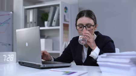 rozsáhlý : Tired woman in suit typing on computer and drinking water, working till late Dostupné videozáznamy