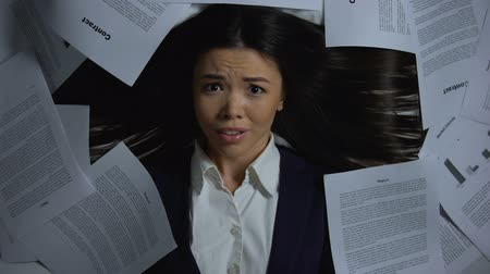 épuisement : Female businesswoman overwhelmed with paperwork, hiding face in horror, closeup