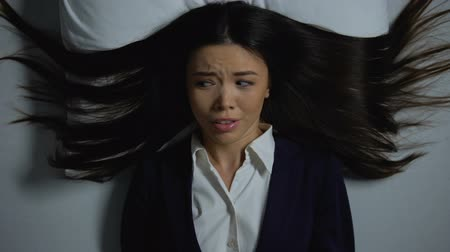 aflição : Asian female in business suit lying in bed, suffering paranoia from overwork Stock Footage