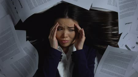 épuisement professionnel : Asian businesswoman covered with documents looking frightened, work overload