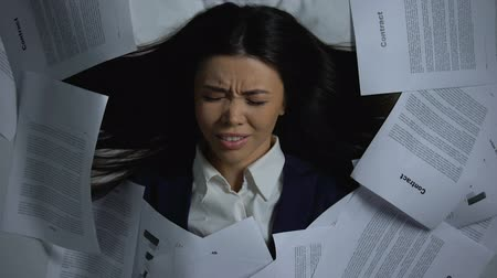 aflição : Asian employee covering herself with documents, despaired of workload, burnout