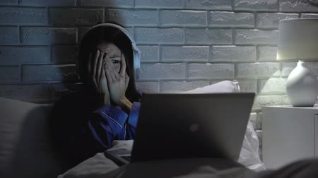 fobi : Young female watching scary movie, hiding face in fear, online film service Stok Video
