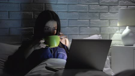 aflição : Asian woman drinking coffee working on laptop late in bedroom, meeting deadline