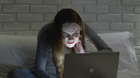 ból pleców : Female working on laptop in bed at night, suffering from neckache, bad posture Wideo