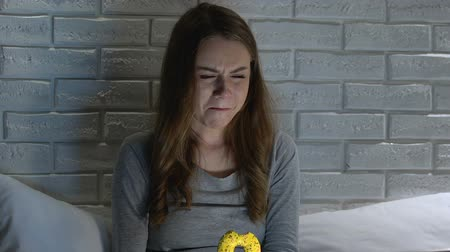 bulimia : Crying woman eating donut at night, bulimia health problems, mental disorder