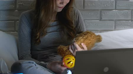 preoccupazione : Crying woman holding baby toy and teddy bear in front of laptop, infertility Filmati Stock