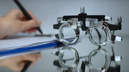 soczewki kontaktowe : Doctor writing eyeglass prescription, vision check with optical trial frame
