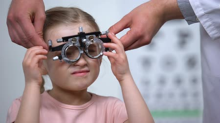 optyk : Doctor wearing optical trial frame on child to diagnose myopia, blurred vision