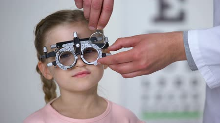 оптический : Ophthalmologist changing lens in eye testing glasses to diagnose child vision