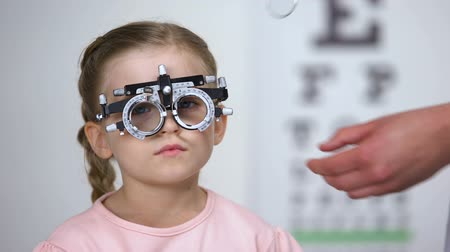 оптический : Child saying no and doctor changing lens in phoropter looking for proper diopter