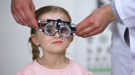 оптический : Optometrist putting phoropter on little girl, child complaining to see nothing Стоковые видеозаписи