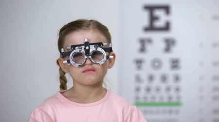 оптический : Pretty girl examining eyes with phoropter in children ophthalmological clinic