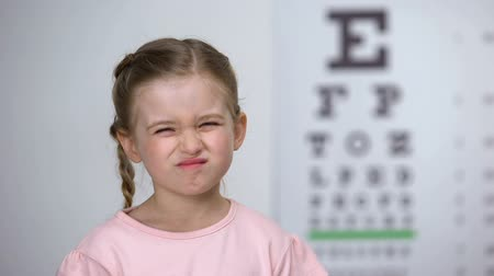 blindness : Little girl squinting eyes, suffering blurred vision, diagnostics of astigmatism