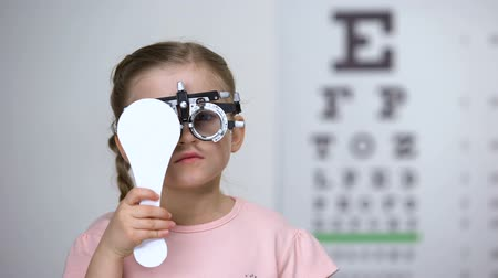 оптический : Child in special glasses with eye closed checking vision, astigmatism diagnosis