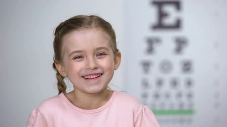 оптический : Adorable child girl laughing after vision test on eye chart, healthy sight Стоковые видеозаписи