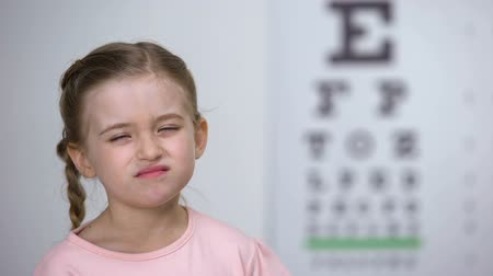 оптический : Little girl trying to read letters from eye chart, diagnostic of nearsightedness